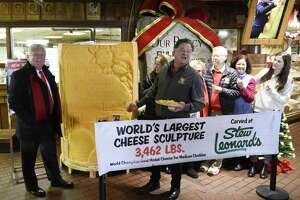 "Norwalk Mayor Harry Rilling, left, joins President and CEO Stew Leonard Jr., center, and the rest of the Leonard family to unveil a 3,462 pound carved block of cheddar cheese at Stew Leonard's grocery store in Norwalk, Conn. Monday, Dec. 10, 2018. Norwalk Mayor Harry Rilling joined the Stew Leonard family to unveil the soon-to-be Guinness Book of World Records' largest cheese sculpture. The mammoth cheddar sculpture has carved into it the longtime Stew Leonard's customer service motto from its ""Customer Service Rock of Commitment."" More than 500 cows contributed milk to the record breaking cheese, which was carved in East Meadow, N.Y."