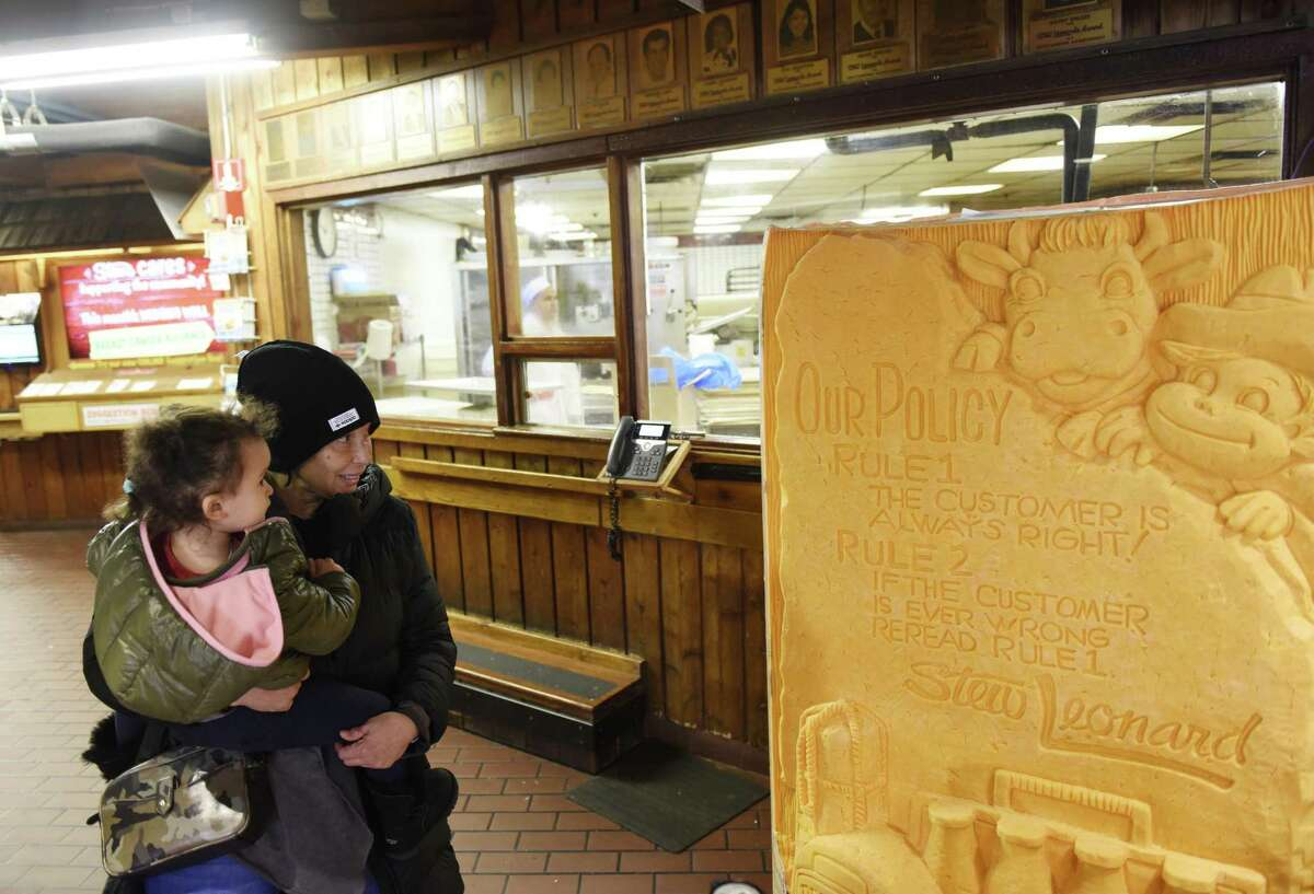 """Fairfield's Dolly Williams and Willow Sahley, 2, gaze upon a 3,462 pound carved block of cheddar cheese displayed at Stew Leonard's grocery store in Norwalk, Conn. Monday, Dec. 10, 2018. Norwalk Mayor Harry Rilling joined the Stew Leonard family to unveil the soon-to-be Guinness Book of World Records' largest cheese sculpture. The mammoth cheddar sculpture has carved into it the longtime Stew Leonard's customer service motto from its """"Customer Service Rock of Commitment."""" More than 500 cows contributed milk to the record breaking cheese, which was carved in East Meadow, N.Y."""