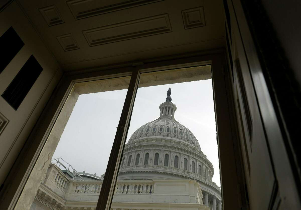 FILE - This Friday, Dec. 28, 2012, file photo shows the Capitol dome on Capitol Hill in Washington. A world-famous symbol of democracy is going under cover, as workers start a two-year, $60 million renovation of the U.S. Capitol dome. Curved rows of scaffolds, like Saturn's rings, will encircle it next spring, enabling contractors to strip multiple layers of paint and repair more than 1,000 cracks and broken pieces. The dome will remain illuminated at night and partly visible through the scaffolding and paint-capturing cloths. But the Washington icon -- and portions of the Rotunda's painted ceiling that lies below -- will be significantly obscured for many months. (AP Photo/Susan Walsh, File)