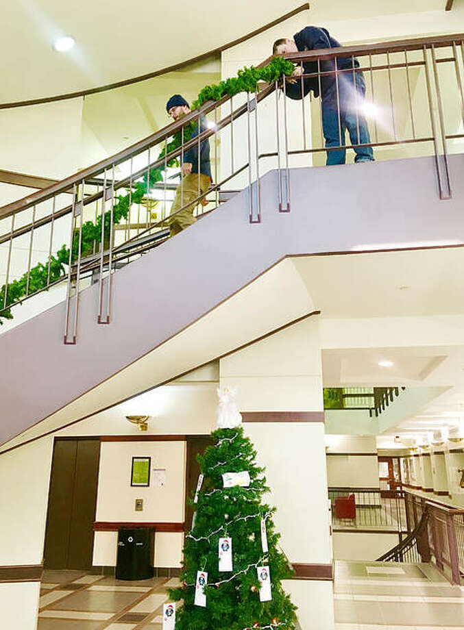 Madison County Facilities Management workers hang garland up on the first floor staircase. Photo: For The Telegraph