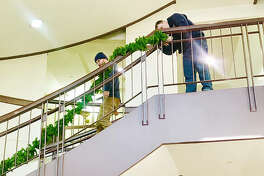 Madison County Facilities Management workers hang garland up on the first floor staircase.