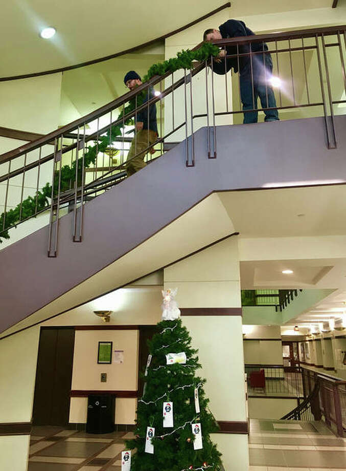 Madison County Facilities Management workers decorate the building with holiday finery. This is the first time in several years that the main lobby and board room have been decorated for Christmas. Photo: For The Intelligencer