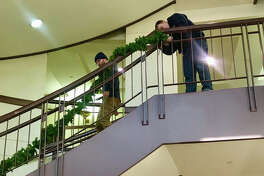 Madison County Facilities Management workers decorate the building with holiday finery. This is the first time in several years that the main lobby and board room have been decorated for Christmas.