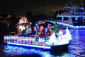 Holiday decorated boats cruise past the Kemah boardwalk during the Christmas Boat Lane Parade Saturday, Dec. 8, 2018.