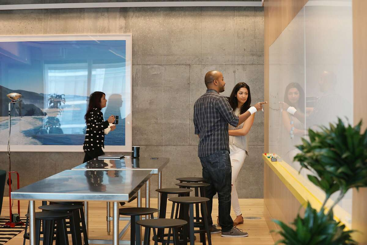Ephraim Tekle (l to r), senior engineering manager and Jasleen Kaur, program manager, talk as Tekle works on a white board near a common dining area at Wework's new dual headquarters in Salesforce Tower on Monday, November 19, 2018 in San Francisco, Calif.
