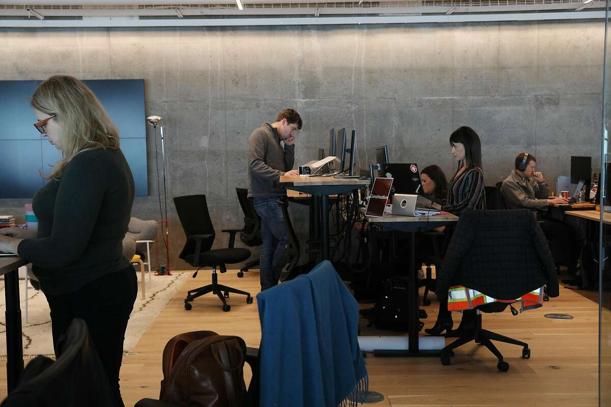 People work standing and sitting at desks at Wework's new dual headquarters in Salesforce Tower on Monday, November 19, 2018 in San Francisco, Calif.