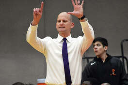 Edwardsville coach Dustin Battas signals a play to his team during the second half against Belleville East.