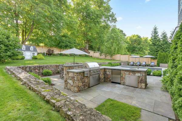 In the fenced backyard there is a large built-in outdoor kitchen.