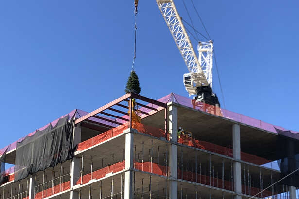 A crane is used to place a 10-foot pine tree on the roof of The Sophie at Bayou Bend, a seven-story condo mid-rise at 6017 Memorial Drive. The ceremonial tree signifies the last beam being placed atop the building during its construction.