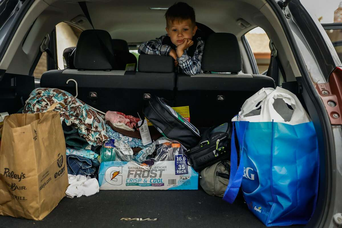 Landon McDaniel, 5, looks down at his family's only belongings (aside from two bags of clothing), ahead of making the move to Oregon after losing his home in the Camp Fire in Paradise, in Chico, California, on Tuesday, Dec. 4, 2018.