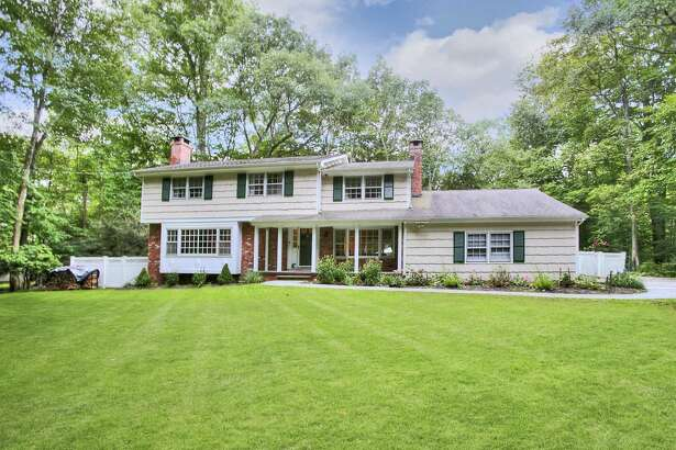 The pale beige shingle house with dark green shutters at 83 Musket Ridge Road in South Wilton sits on a private setting of two acres convenient to local amenities.