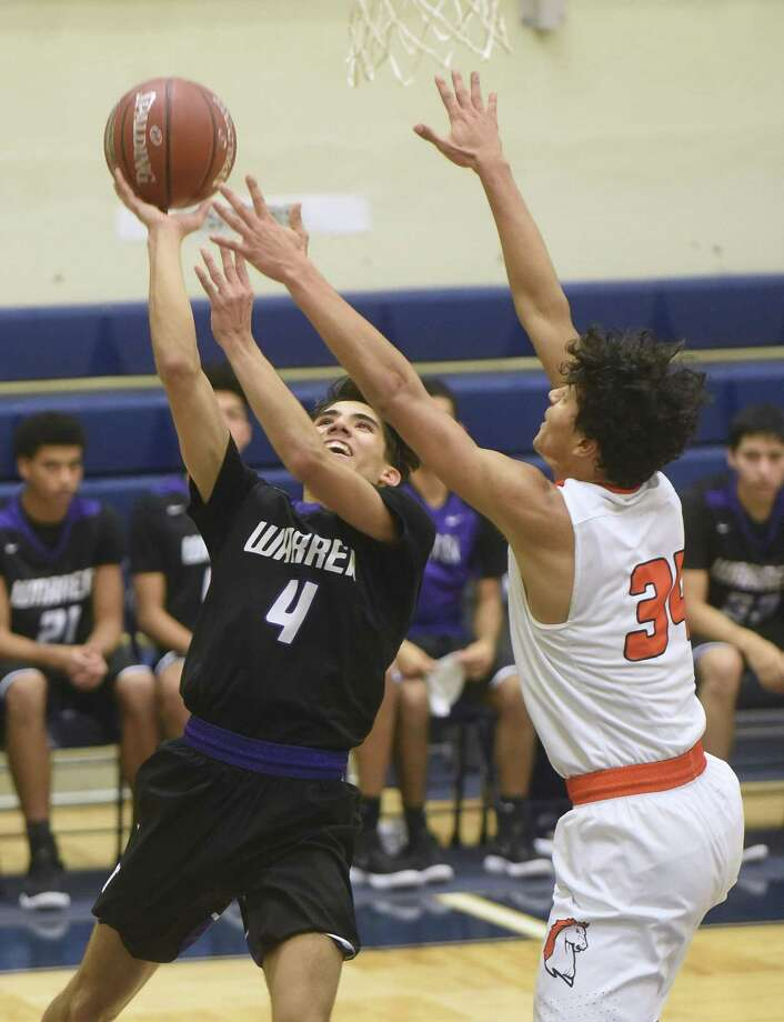 Warren's Isaac Gamboa, left, scored 24 points and snared six rebounds in a district victory over Stevens. Gamboa made six 3-pointers. Photo: Billy Calzada /Staff Photographer / San Antonio Express-News
