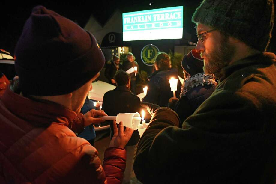 Organizer Sean Collins, left, lights a candle for Brandon Bissell-Evans of Albany as protesters hold a candlelight vigil outside a fundraiser at Franklin Terrace Ballroom on Monday, Dec. 10, 2018 in Troy, N.Y. The protesters were uniting against Mayor Patrick Madden, who opposes efforts to make Troy a sanctuary city. (Lori Van Buren/Times Union) Photo: Lori Van Buren, Albany Times Union / 20045681A