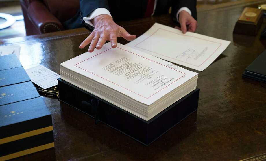President Donald Trump signs the Tax Reform Bill in the Oval Office of the White House in Washington, Dec. 22, 2017. Tax cuts when there are deficits need to be offset by spending decreases. Photo: DOUG MILLS /NYT / NYTNS