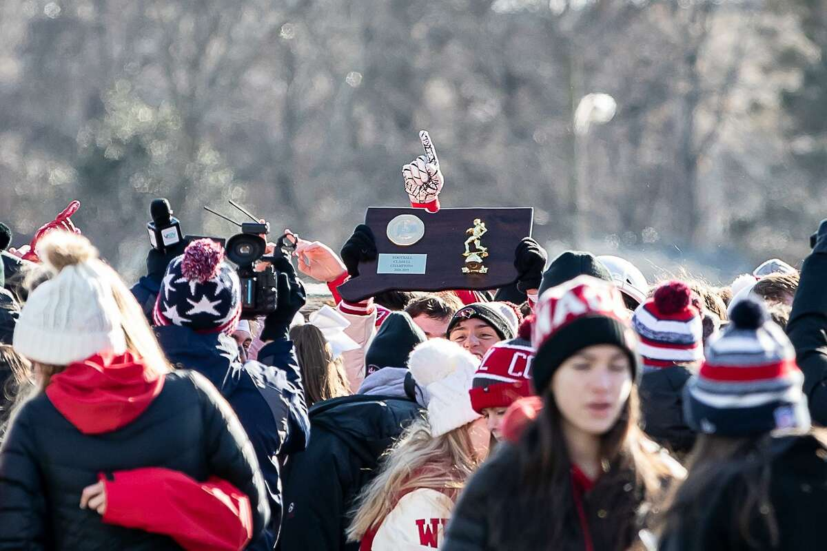 Greenwich players and fans celebrate a victory with the State Championship Plaque after the Class LL State Championship game between on New Canaan and Greenwich on December 8, 2018 at Boyle Stadium in Stamford, CT.