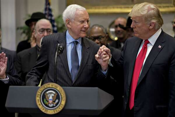 Sen. Orrin Hatch, R-Utah, and President Donald Trump hold hands during a signing ceremony for H.R. 1551, the Hatch-Goodlatte Music Modernization Act, at the White House in Washington on Oct. 11, 2018.