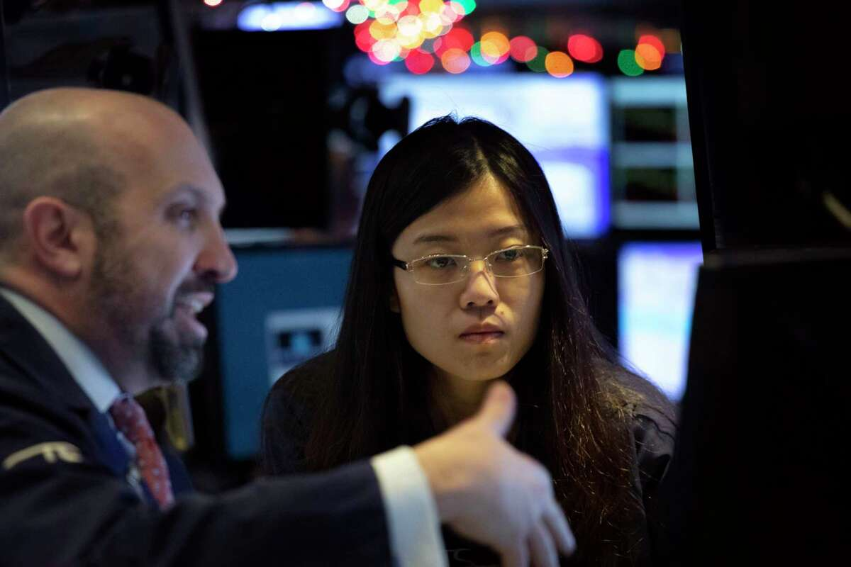 Stock traders James Denaro, left, and Vera Liu follow stock prices at the New York Stock Exchange, Monday, Dec. 10, 2018. Stocks are wobbling between small gains and losses in the early going on Wall Street as trading settles down following huge losses last week. (AP Photo/Mark Lennihan)