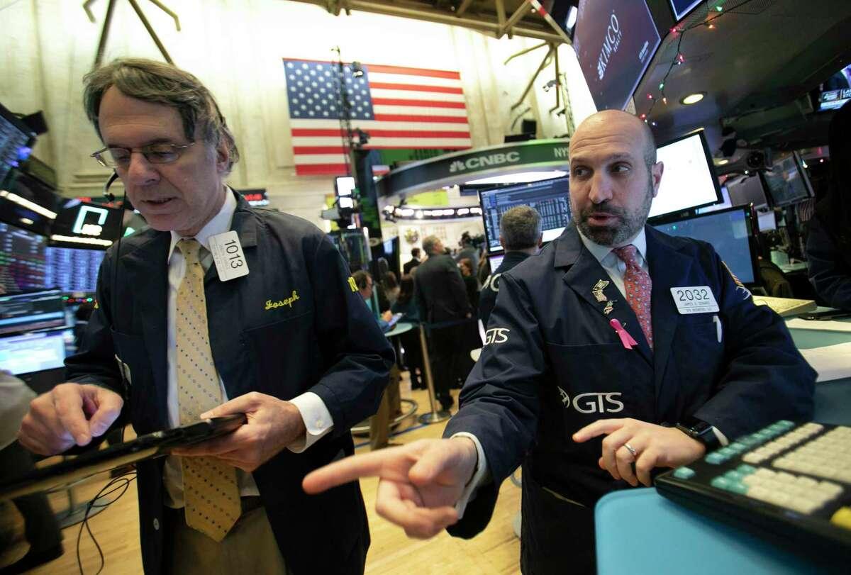 James Denaro, right, talks stock prices at the New York Stock Exchange, Monday, Dec. 10, 2018. (AP Photo/Mark Lennihan)