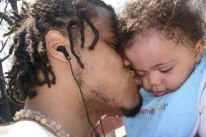 In this undated photo provided by Angelique Negroni-Kearse, Andrew Kearse kisses his son, Justice Kearse. Andrew Kearse died on May 11, 2017 after a foot pursuit with Schenectady, N.Y., police. After his arrest, he complained of dizziness and difficulty breathing, then lost consciousness on the drive to the police station.