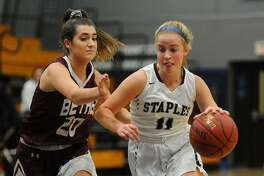 Staples' Elle Fair drives to the basket defended by Bethel's Anna Riolo on Monday at Staples High School.