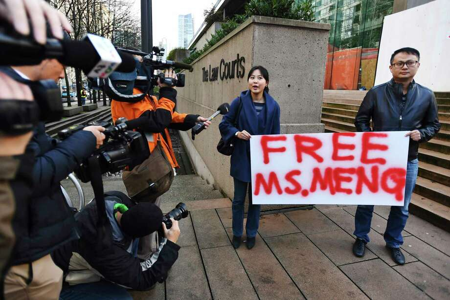 People hold a sign at a Vancouver, British Columbia courthouse prior to the bail hearing for Meng Wanzhou, Huawei's chief financial officer on Monday, December 10, 2018. Meng Wanzhou was detained at the request of the U.S. during a layover at the Vancouver airport on Dec. 1.(Jonathan Hayward/The Canadian Press via AP) Photo: Jonathan Hayward / The Canadian Press