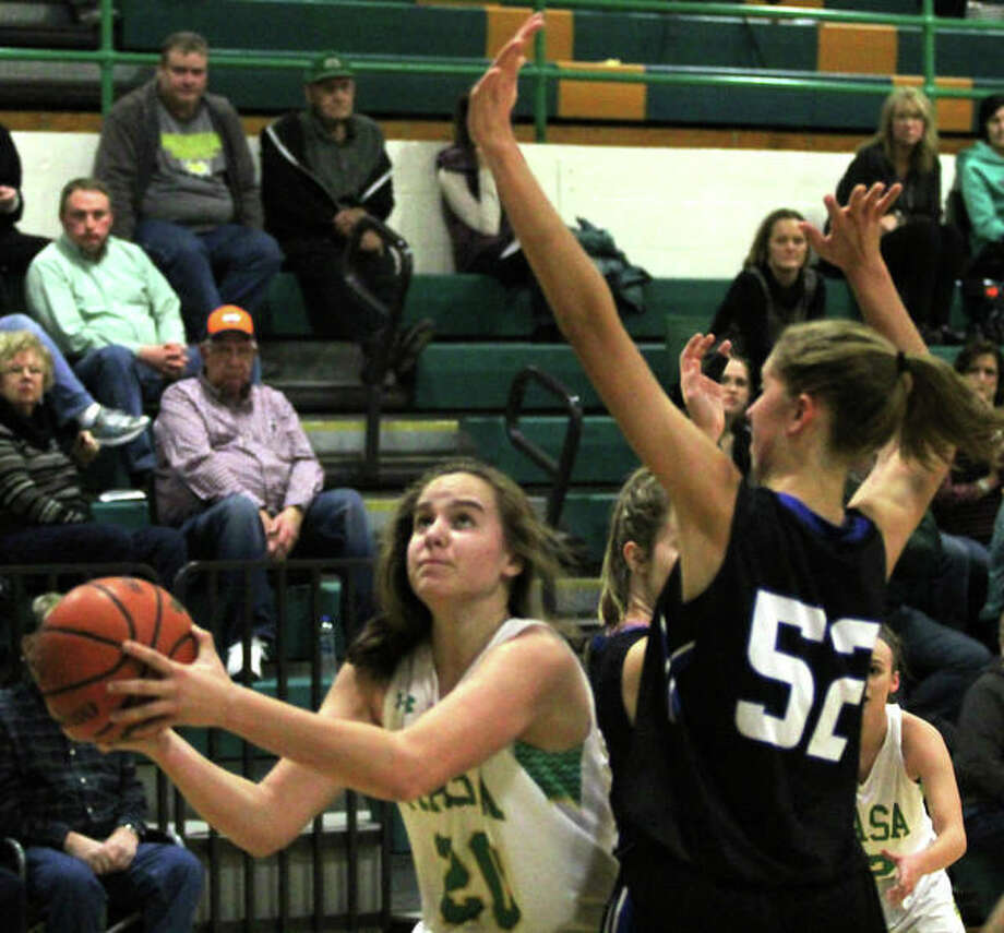 Southwestern's Korrie Hopkins ducks under Greenville's 6-foot-4 Megan Halleman (52) for a shot during Monday's SCC girls basketball game in Piasa. Photo: Greg Shashack / The Telegraph