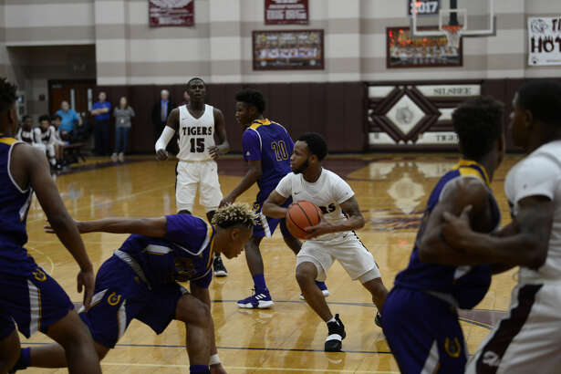 Silsbee junior guard Braelon Bush cuts through the Center defense and finds an open man during the Tigers home win on Monday night. Photo by Matt Faye/The Enterprise