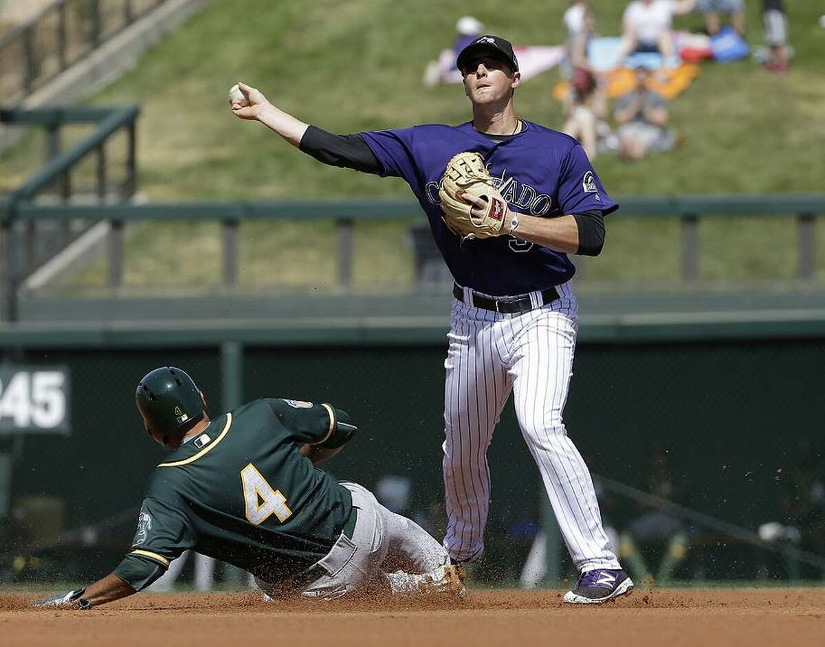 Colorado Rockies second baseman DJ LeMahieu throws to first base after forcing out Oakland Athletics' Coco Crisp (4) during the first inning of a spring training baseball game in Scottsdale, Ariz., Tuesday, March 15, 2016.