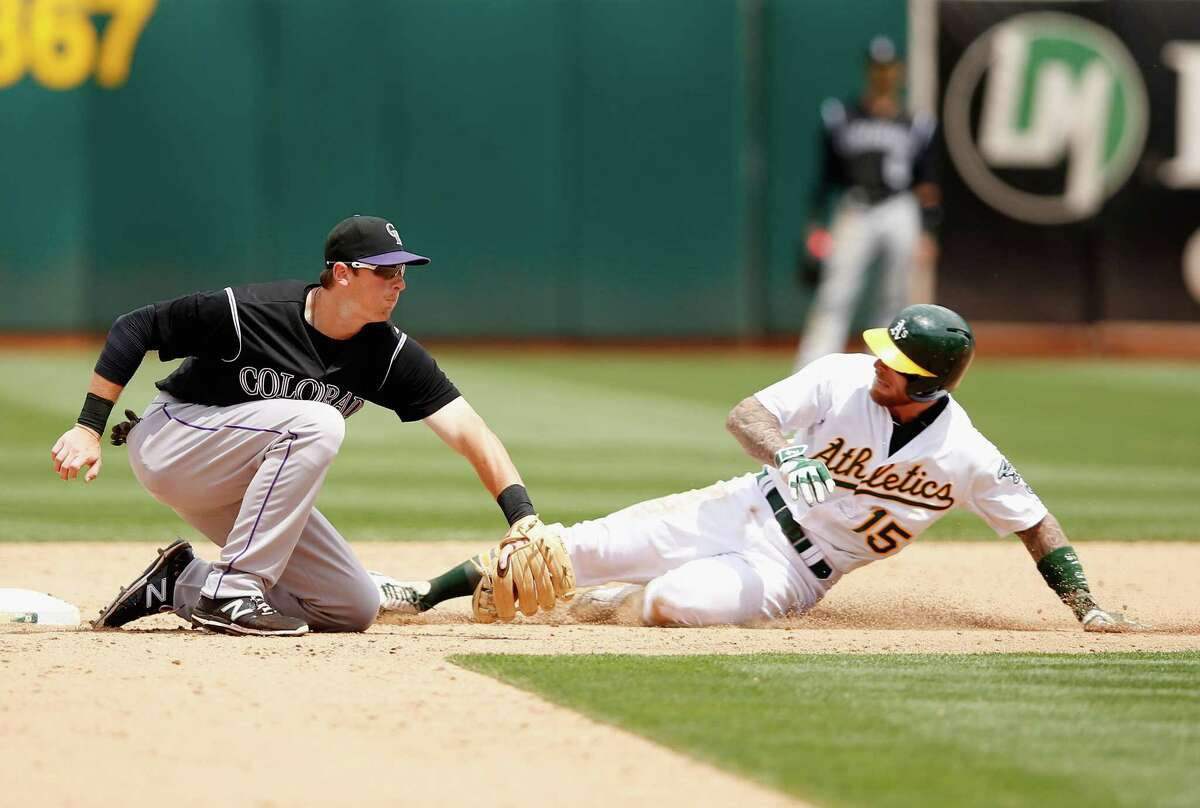 Brett Lawrie #15 of the Oakland Athletics beats the tag of DJ LeMahieu #9 of the Colorado Rockies to advance to second base on a wild pitch in the sixth inning at O.co Coliseum on July 1, 2015 in Oakland, California.