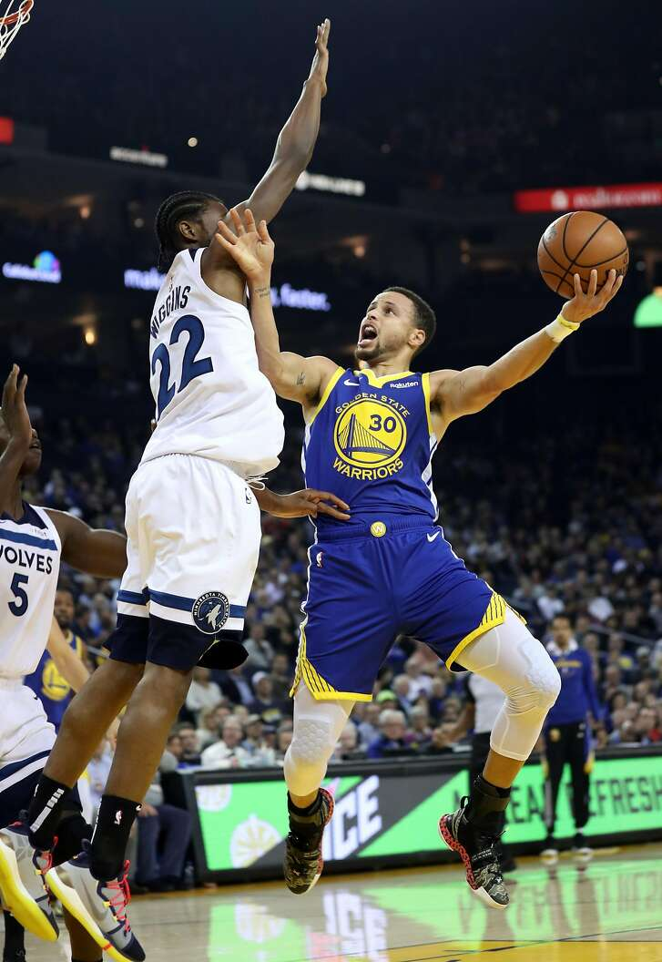 Golden State Warriors' Stephen Curry drives against Minnesota Timberwolves' Andrew Wiggins in 2nd quarter during NBA game at Oracle Arena in Oakland, Calif. on Monday, December 10, 2018.