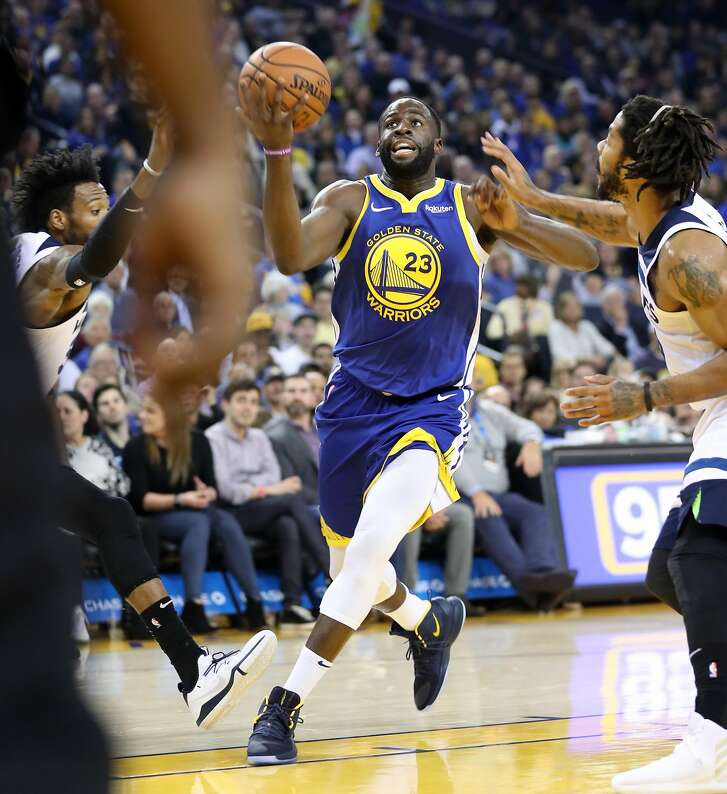 Golden State Warriors' Draymond Green drive stop the basket for a 2nd quarter basket against Minnesota Timberwolves' Derrick Rose and Robert Covington during NBA game at Oracle Arena in Oakland, Calif. on Monday, December 10, 2018.