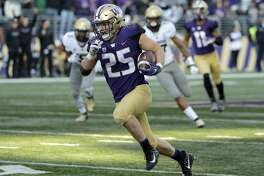 FILE - In this Oct. 20, 2018, file photo, Washington linebacker Ben Burr-Kirven (25) runs after he intercepted a pass thrown by Colorado quarterback Steven Montez during the second half of a game in Seattle. Burr-Kirven was named to the 2018 AP All-America NCAA college football team, Monday, Dec. 10, 2018. (AP Photo/Ted S. Warren, File)