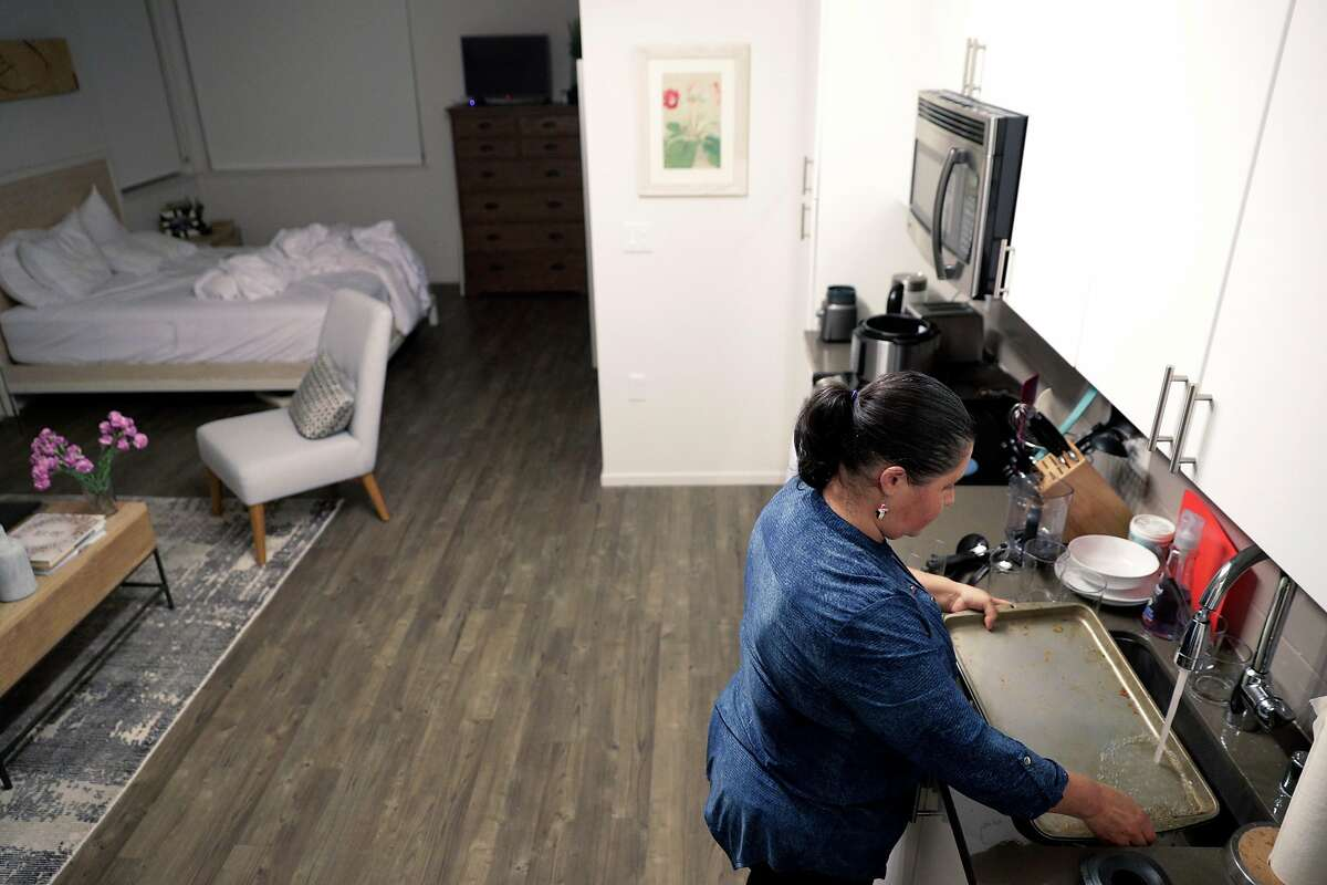 Lourdes Dobarganes scrubs a sheet pan as she cleans the studio apartment of one of her clients in San Francisco, Calif., on Monday, December 10, 2018. Dobarganes is looking into using Alia, a new service for people who clean houses to have their employers chip in to provide some benefits for them, such as paid time off or life insurance.