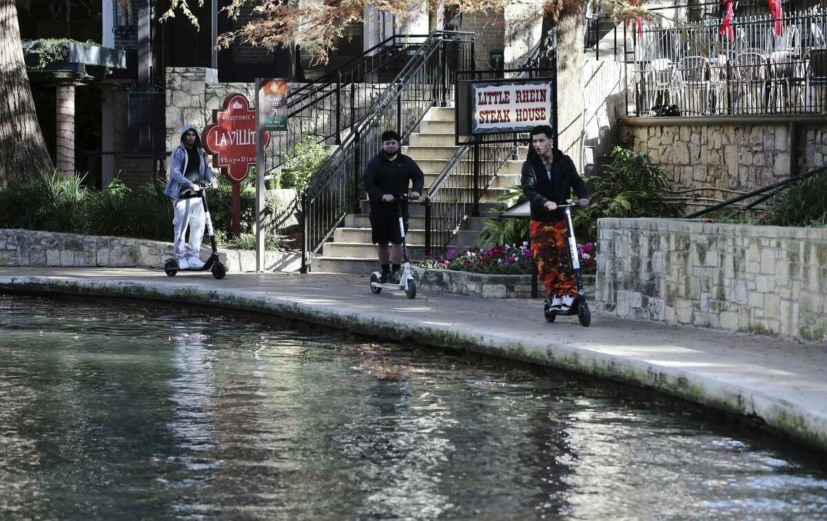 Three electric scooter riders are seen on the River Walk near La Villita on Dec. 4, 2018. The city ordinance bans scooters there and on Alamo Plaza.