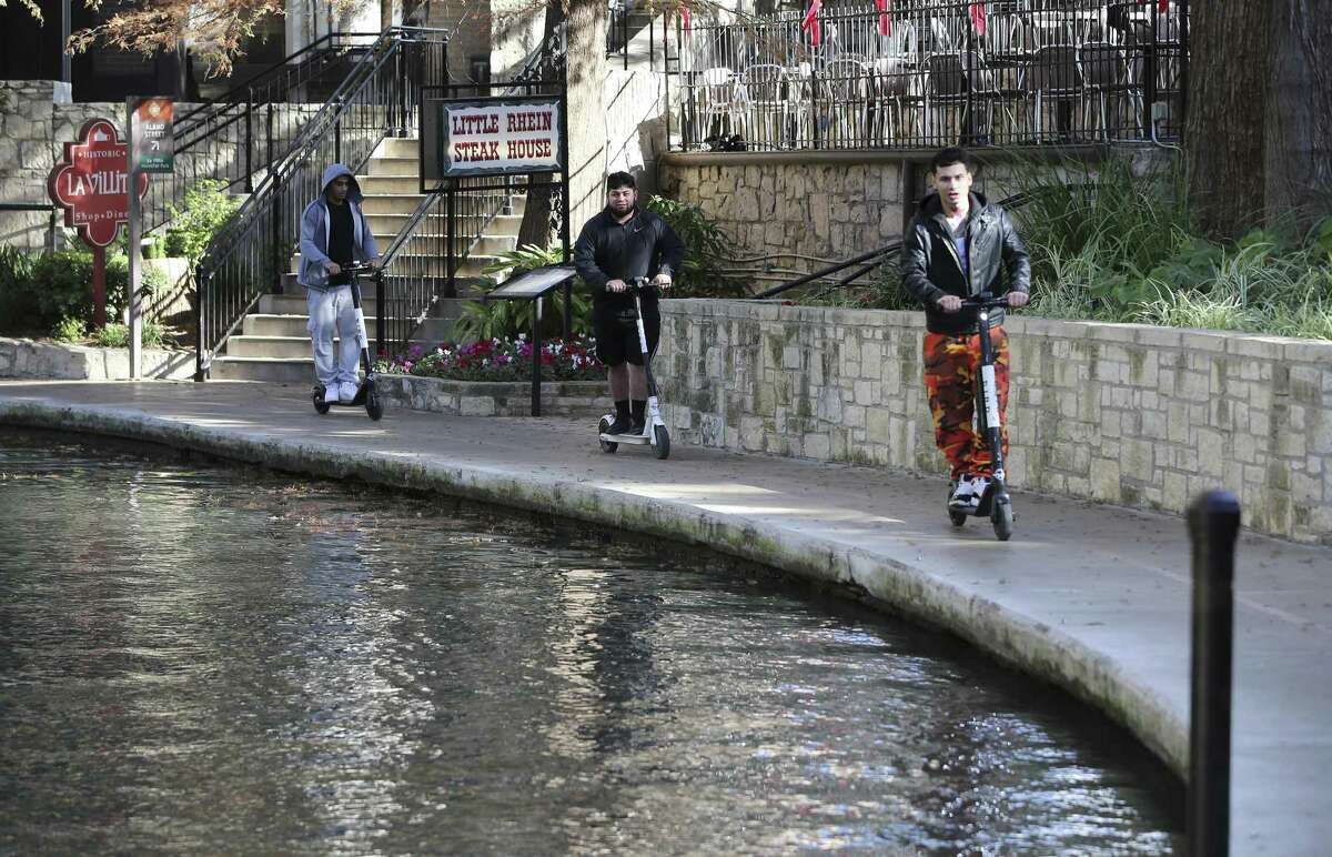 The city has banned scooters from the River Walk, where these three riders were seen near La Villita on Dec. 4, 2018. Critics of scooters think some rental companies and riders are flouting city rules. San Antonio says it plans to hire four workers to step up enforcement.