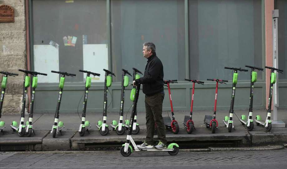 Electric scooters line some San Antonio downtown streets, such as Commerce Street. New Braunfels recently enacted an indefinite ban on the vehicles. Photo: Kin Man Hui /Staff Photographer / ©2018 San Antonio Express-News