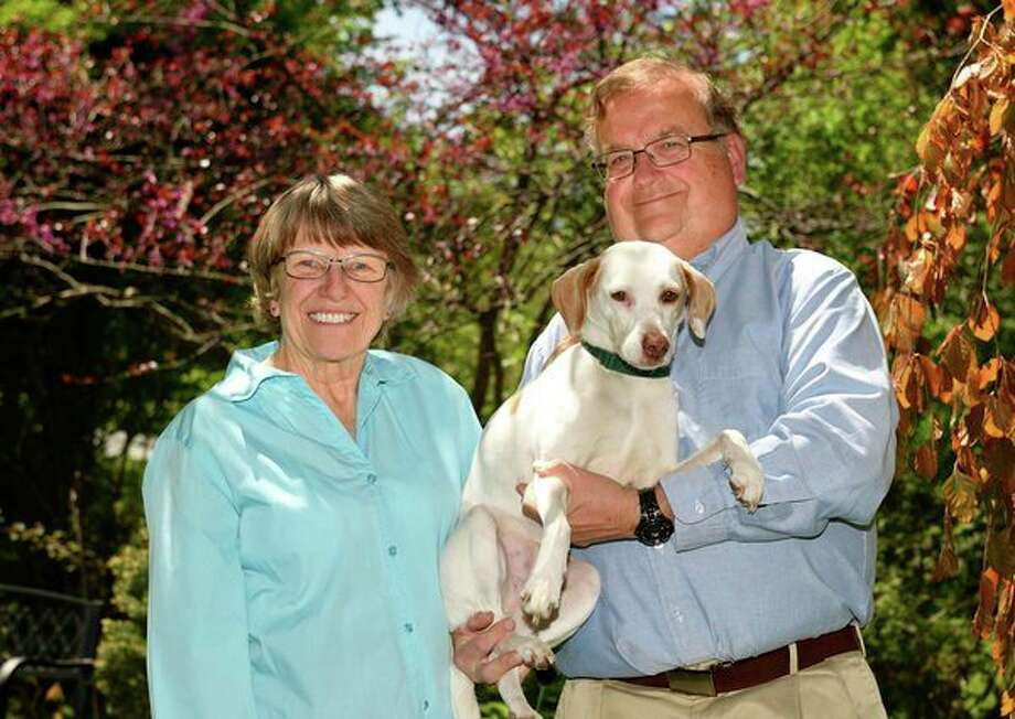 Michigan State University alumna Jane Wall Lacher and her husband, Ronald, stand with their beloved rescue dog, Belle, in the front garden of Jane's childhood home. The Lacher's estate gift will fund an endowed faculty position in nursing research and a scholarship for veterinary students. (Photo provided)