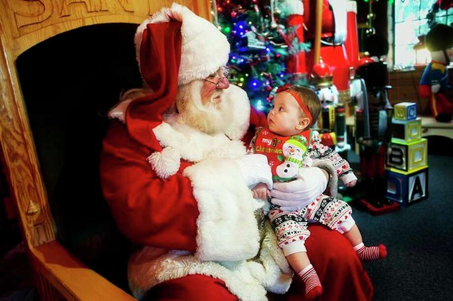 Agnes Kernstock of Auburn, 8 months, takes a look at Santa Claus while sitting on his lap inside the Santa House on Monday afternoon. The Santa House is open every day through Dec. 23 from 1:30 p.m. - 4:30 p.m. and 6 p.m. - 9 p.m., as well as from 9 a.m. - noon on Sundays. (Katy Kildee/kkildee@mdn.net)