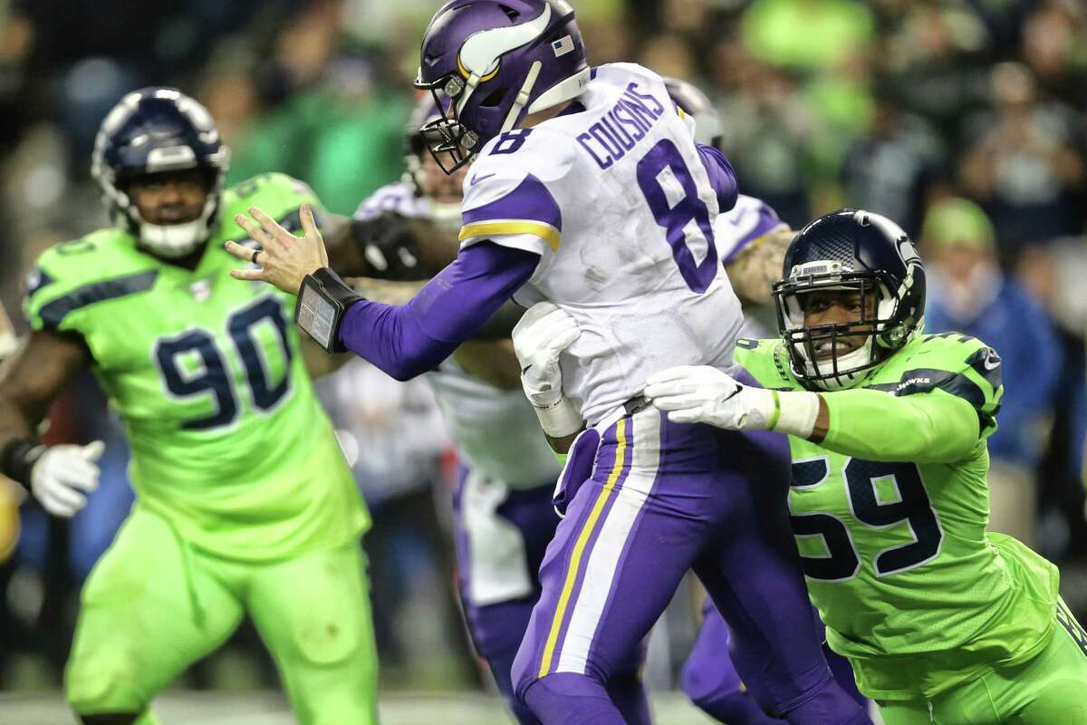 Seahawks defensive lineman Jacob Martin (59) strips the ball from Vikings quarterback Kirk Cousins as he tries to pass leading to a fumble that was returned for a touchdown by Seahawks corner back Justin Coleman during the fourth quarter of Seattle's game against the Minnesota Vikings at CenturyLink Field, Dec. 10, 2018.