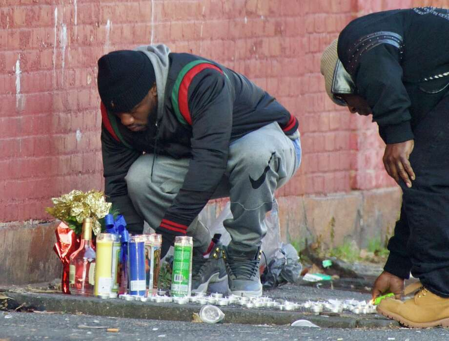 Mourners light candles in memory of a 28-year-old shooting victim at the corner of Judson and Second streets in Albany, NY, on Tuesday, Dec. 11, 2018. (Skip Dickstein/Times Union) Photo: Skip Dickstein/Times Union_