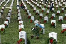 Lane Austin, 6, of Virginia Beach, Va., carries a wreath to grave during Wreaths Across America at Arlington National Cemetery, Saturday, Dec. 12, 2015 in Arlington, Va. Organizers estimated that volunteers placed 240,815 wreaths at Arlington.(AP Photo/Alex Brandon)
