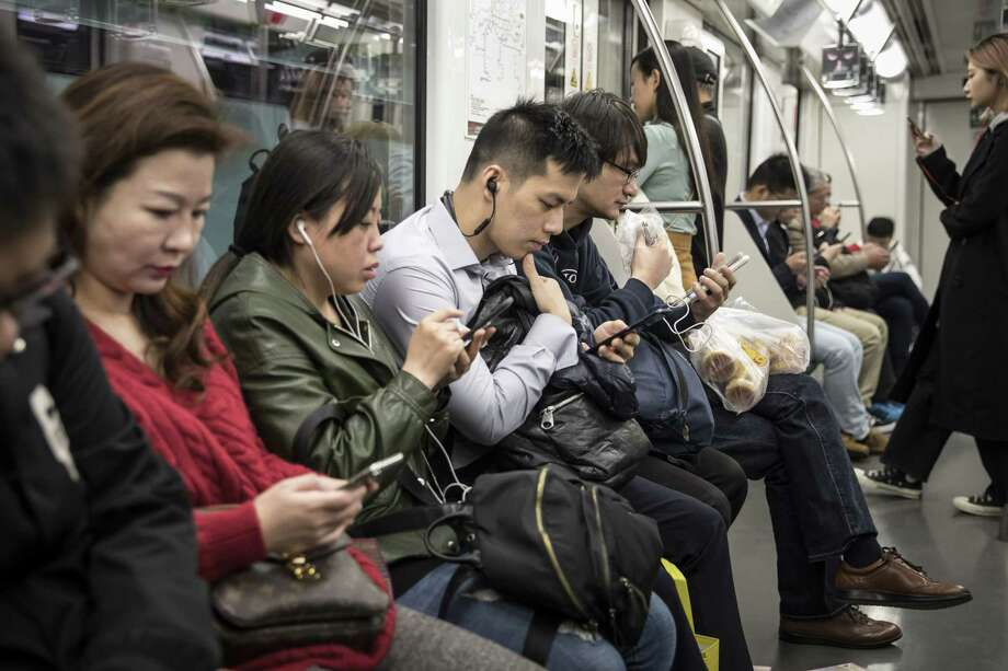Subway commuters look at smartphones in Shanghai on Nov. 27, 2018. Photo: Qilai Shen/Bloomberg / Bloomberg
