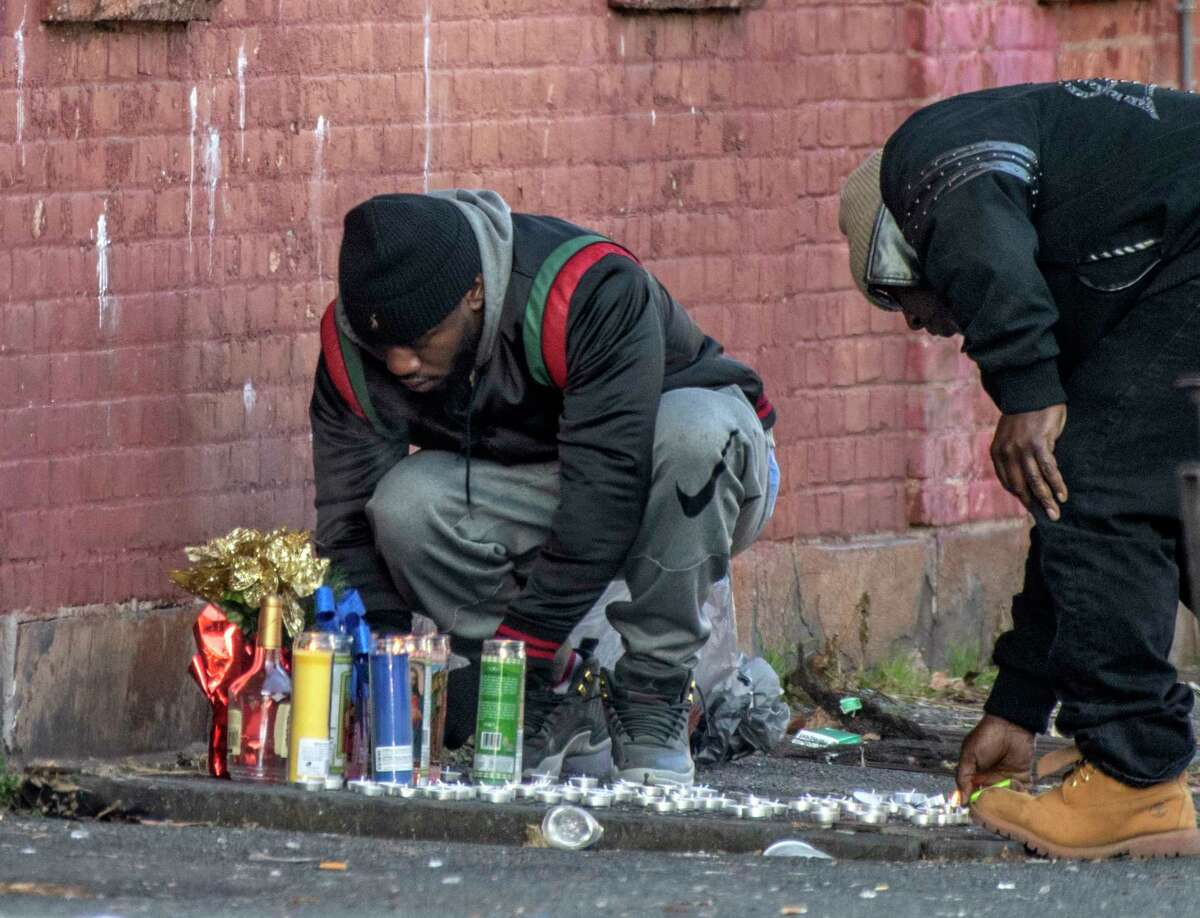 Mourners light candles at a makeshift memorial to a shooting victim at the corner of Judson St. and Second St. Tuesday Dec. 11, 2018 in Albany, N.Y. (Skip Dickstein/Times Union)