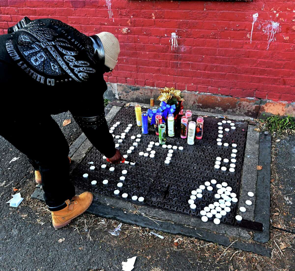 A mourner lights candles at a makeshift memorial to a shooting victim at the corner of Judson St. and Second St. Tuesday Dec. 11, 2018 in Albany, N.Y. (Skip Dickstein/Times Union)