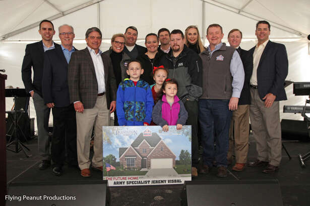 Army veteran Jeremy Visbal (black and gray jacket) stands with his family as he is presented a mortgage-free home.
