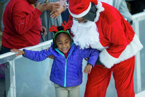 Santa, Fox 26 general manager D'Artagnan Babel, helps Mya Thornton, 7, keep her balance while learning to ice skate during the 3rd annual Year Of Joy Holiday Ice Skating Party at the ICE powered by Green Mountain Energy at Discovery Green in downtown Houston, Monday, Dec. 10, 2018.