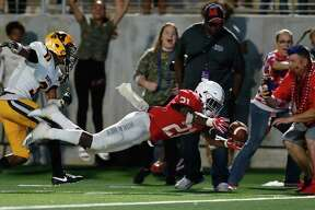 Manvel Mavericks Ladarius Owens (21) dives for the pylon after being hit by Fort Bend Marshall Buffalos Drew Conley (3) in the fourth quarter during the high school football game between the Fort Bend Marshall Buffalos and the Manvel Mavericks at Freedom Field in Rosharon, TX on Friday, September 21, 2018.
