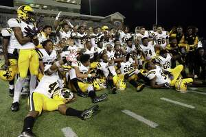 Fort Bend Marshall players gather for a victory photo after defeating Huntsville 47-43 in their 5A Division 2 regional playoff game Thursday, Dec. 6, at Cy-Fair FCU Stadium in Cypress.