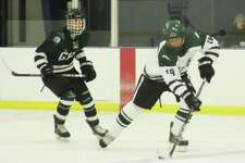 Spectrum/New Milford High School hockey team recently played home against Guilford. Unfortunately, the Green Wave lost the Jan. 10, 2018 game 9-4. Above, junior Evan Golembeske skates the puck up the ice past the Guilford defense to get the first goal for New Milford. Courtesy of Katie Alzapiedi