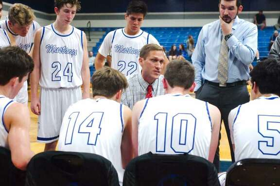 Friendswood head basketball coach Cliff Owens (center) resigned Monday. Caleb Marburger (back right) will assume interim duties as head coach.
